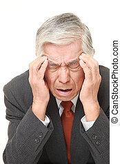 senior Japanese businessman suffers from headache
