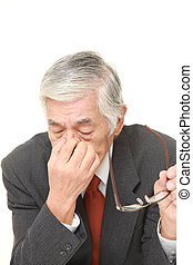 senior Japanese businessman suffers from Asthenopia