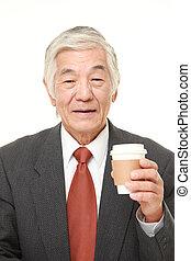 senior Japanese businessman takes a coffee break
