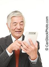 senior Japanese businessman using tablet computer