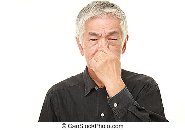 senior Japanese man holding his nose because of a bad smell...