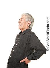 senior Japanese man suffers from lumbago - studio shot of...