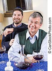Senior Jewish man, adult son celebrating Hanukkah - Senior...