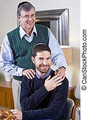 Senior Jewish man with adult son wearing yarmulkes -...
