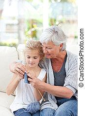 Senior knitting with her granddaughter