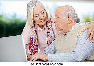 senior koppel, beschouwende elkaar, terwijl, gebruikende laptop