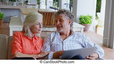 senior koppel, het bespreken, op, draagbare computer, op, sofa, 4k