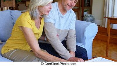 senior koppel, het bespreken, op, rekeningen, op, sofa, 4k