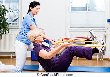 senior koppel, in, fysiotherapie, doen, oefening, met, hula hoop