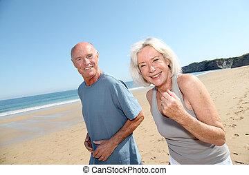 senior koppel, jogging, op, een, zandig strand