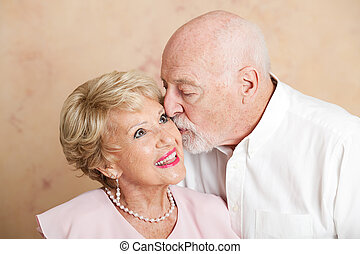 senior koppel, -, kus op de wang