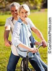 senior koppel, op een fiets, buitenshuis
