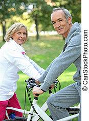 senior koppel, op een fiets
