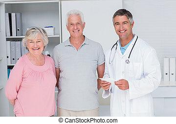 senior koppel, staand, kliniek, arts, vrolijke