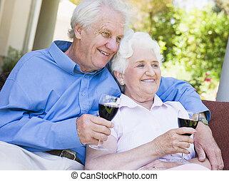 senior koppel, zittende , buitenshuis, hebben, een, glas van rode wijn