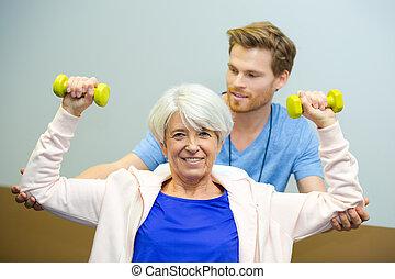senior kvinde, ophævelse, dumbbells, ind, duelighed, hos, en, træner