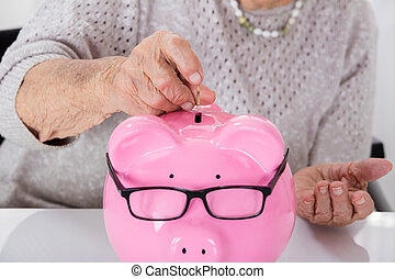 senior, kvinnas hand, infogar, mynt, in, piggybank