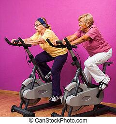 Senior ladies at spinning session. - Portrait of two senior...