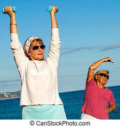 Senior ladies doing fitness exercises on beach.