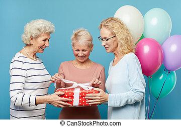 Senior ladies opening gift box together