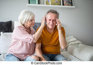 Senior lady comforting his husband with headache