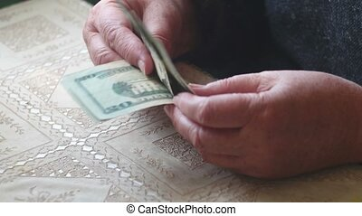 Senior lady counting twenty dollar banknotes, selective...