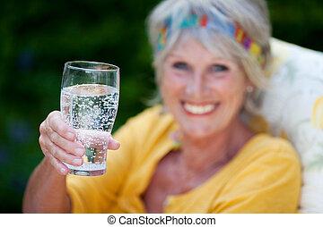senior lady drinking sparkling water in summer