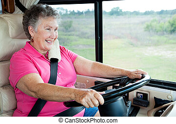 Pretty senior woman enjoys driving her motor home.