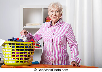Senior lady during folding laundry - Senior lady wearing...