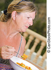 Senior Lady Enjoying a Bowl of Paella Whilst on Vacation