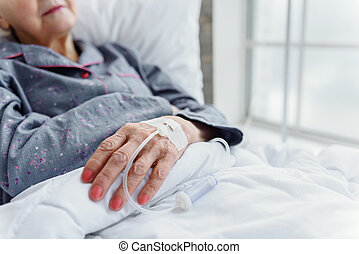 Senior lady is on drip bulb reclining in cot