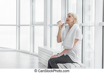 Senior lady is very thirsty after training