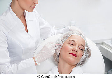 Senior lady is visiting cosmetologist to get botox
