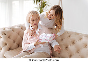 Senior lady receiving a gift from her daughter