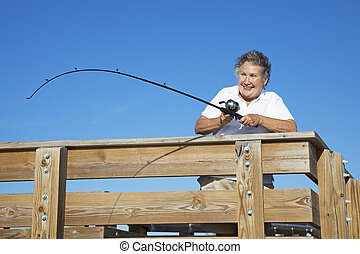 Senior Lady Reels in Fish
