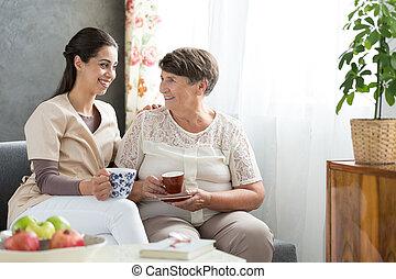 Senior lady serving tea - Grateful senior lady serving tea...