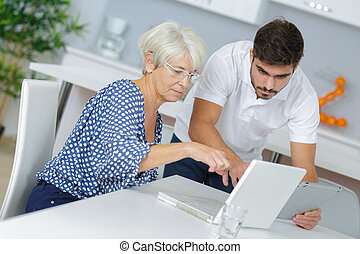 senior lady sitting with a laptop beside her grandson
