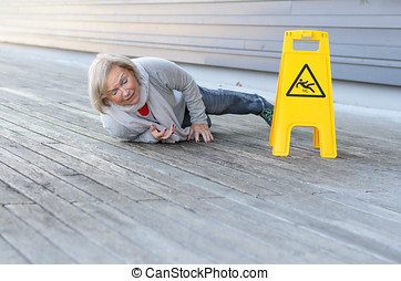 Senior lady slipping and falling on a wet surface with a...