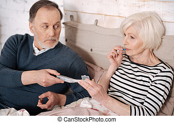 Senior lady taking pills from her husband