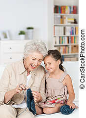 Senior lady teaching her granddaughter to knit as they relax...