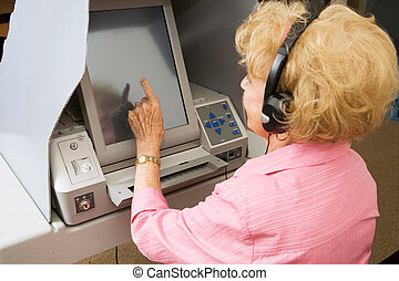 Senior Lady Votes on Touch Screen - Senior lady using...
