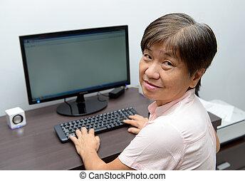 Senior lady with desktop computer