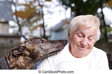 Senior lady with brindle greyhound in backyard