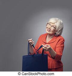 Senior lady with shopping bag - Smiling senior lady with...