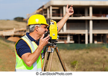 land surveyor talking on walkie talkie