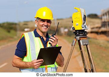 land surveyor - senior land surveyor working at road ...