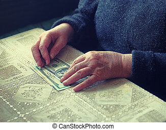 Senior latino female with small amount of money, toned image, colorized, selective focus, very shallow dof