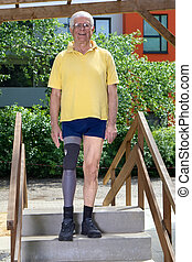 Senior leg amputee standing on staircase of training course for practicing