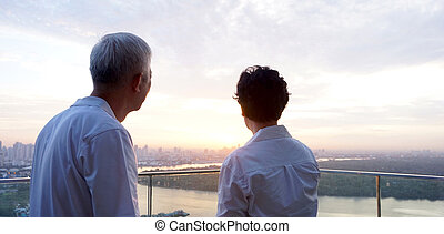senior looking at sunrise together over city skyline