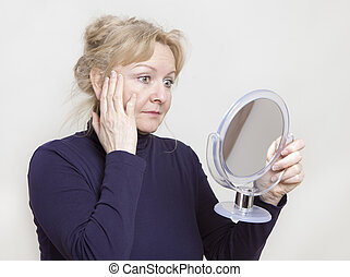 Senior looking in mirror - an older woman looking in a hand...